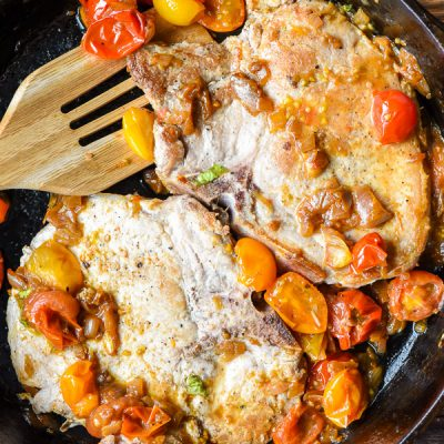 Two Pork Chops in a skillet with burst tomatoes
