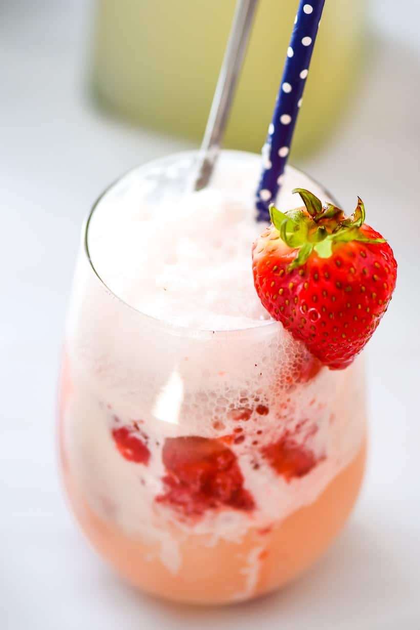 Strawberry Lemonade Ice Cream Floats with a paper straw and strawberry garnish