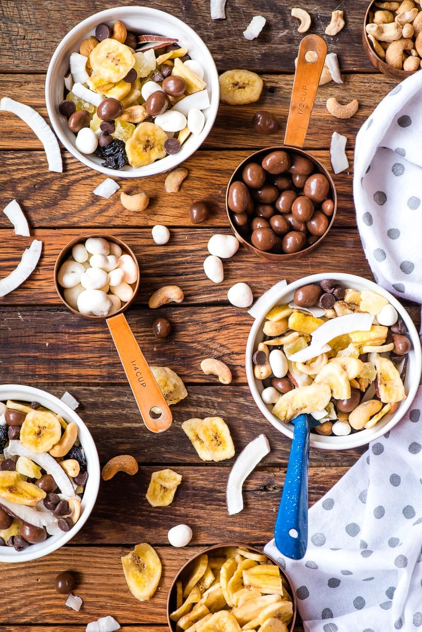 Bowls of Chunky Monkey Trail Mix with spoons and measuring cups
