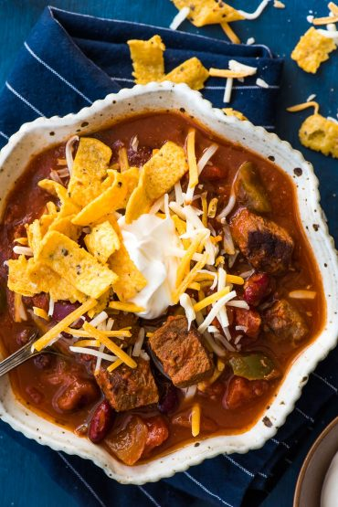 Slow Cooker Steak Chili with cheese, sour cream, and fritos