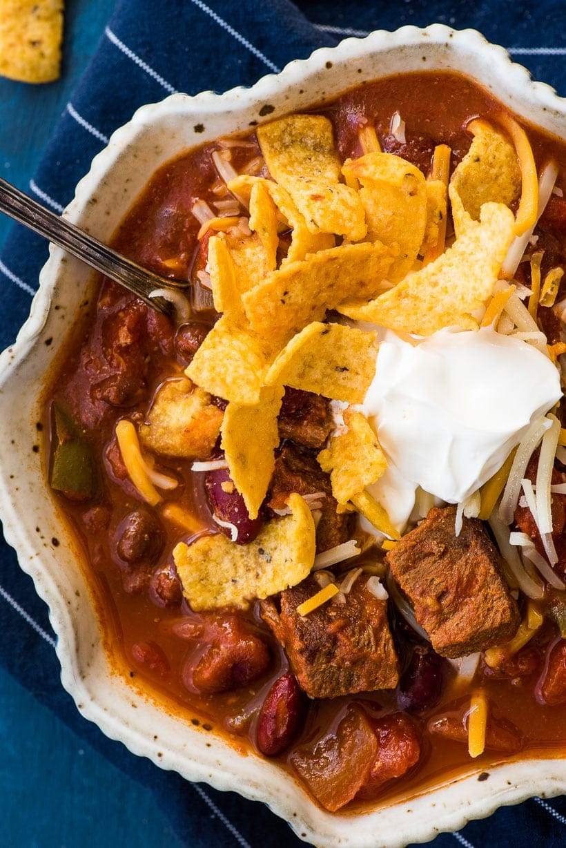 Slow Cooker Steak Chili in a bowl with sour cream and fritos