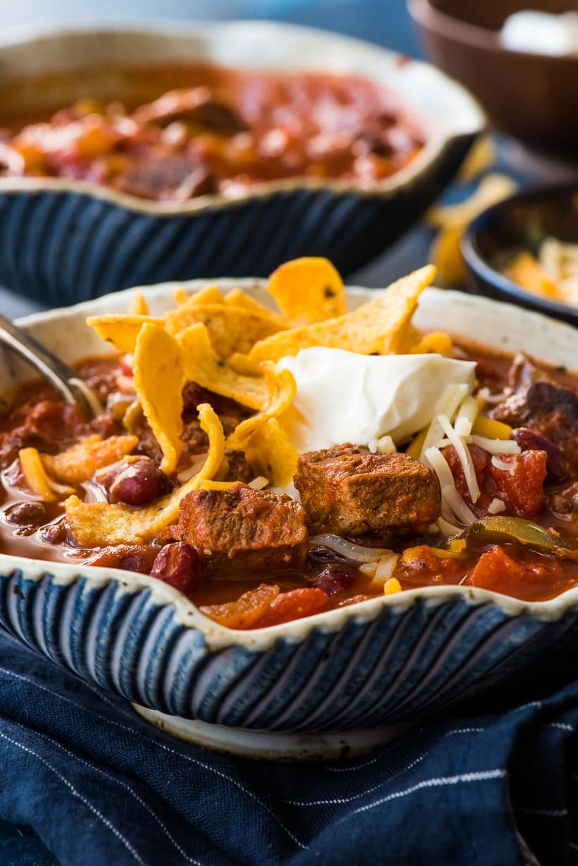 Close up of Slow Cooker Steak Chili with sour cream and fritos on top