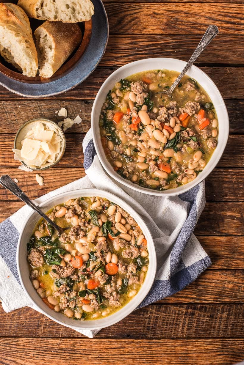 two bowls of italian sausage stew with white beans