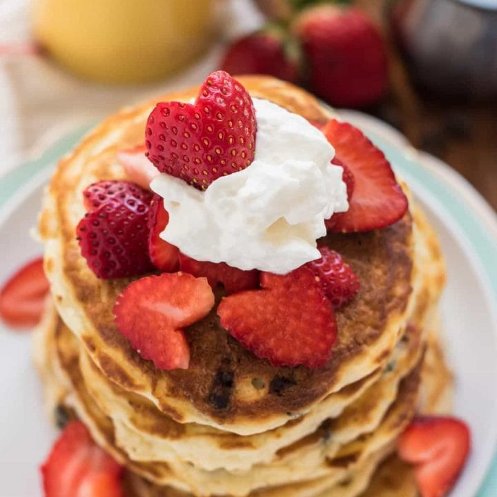 Stack of chocolate chip pancakes topped with strawberry hearts and whipped cream.