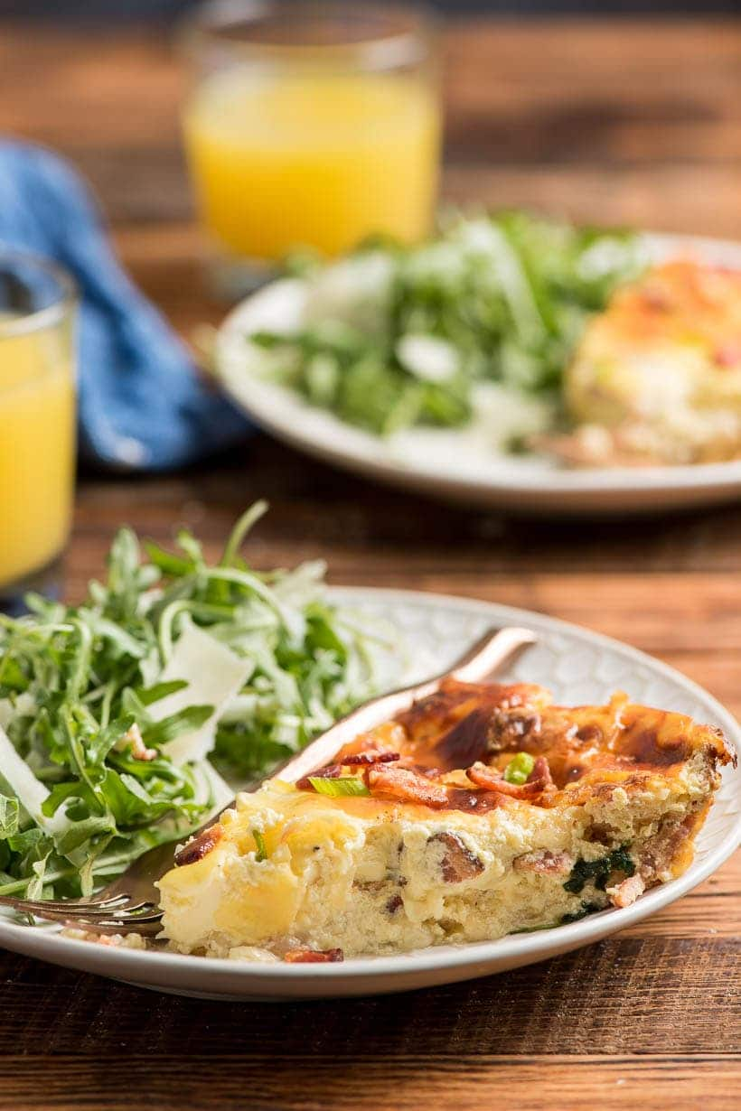 Slice of Crustless Quiche Lorraine plated with simple arugula salad