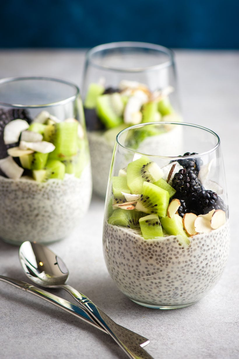 Three glasses filled with overnight chia pudding with fruit on top