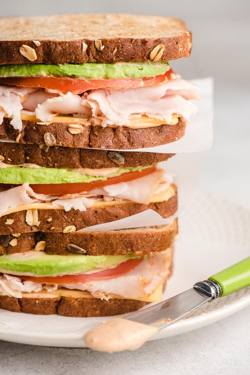 Three turkey avocado sandwiches stacked on a plate