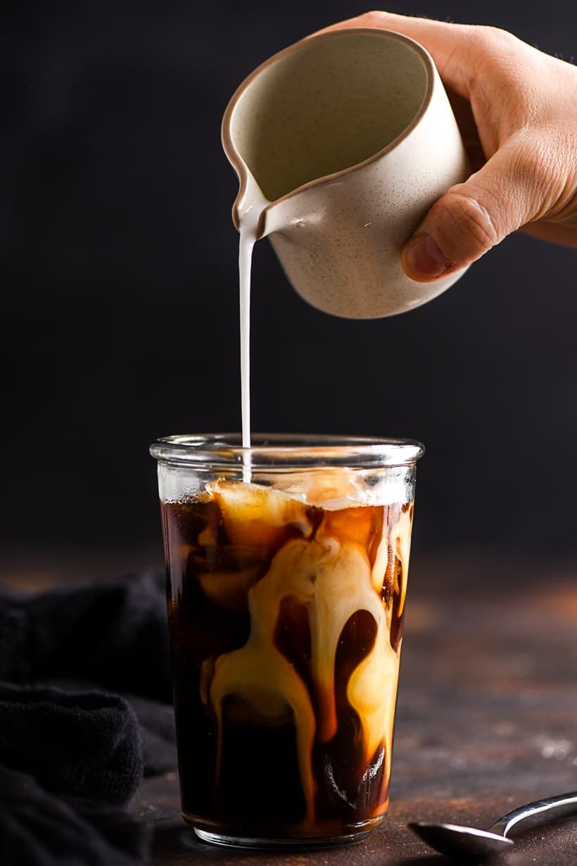 coconut milk poured into a glass of vanilla iced coffee