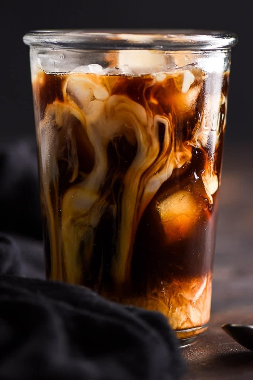 swirls of coconut milk in iced coffee