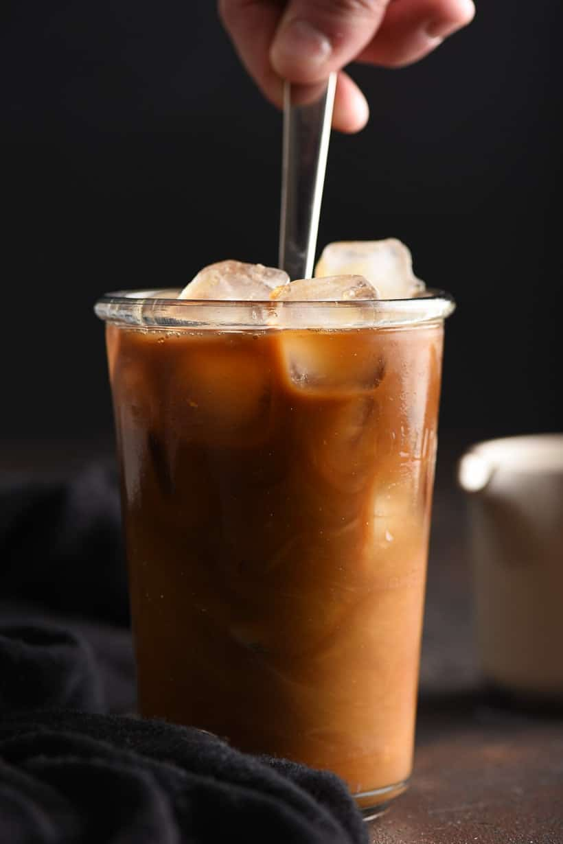 vanilla iced coffee stirred with a spoon