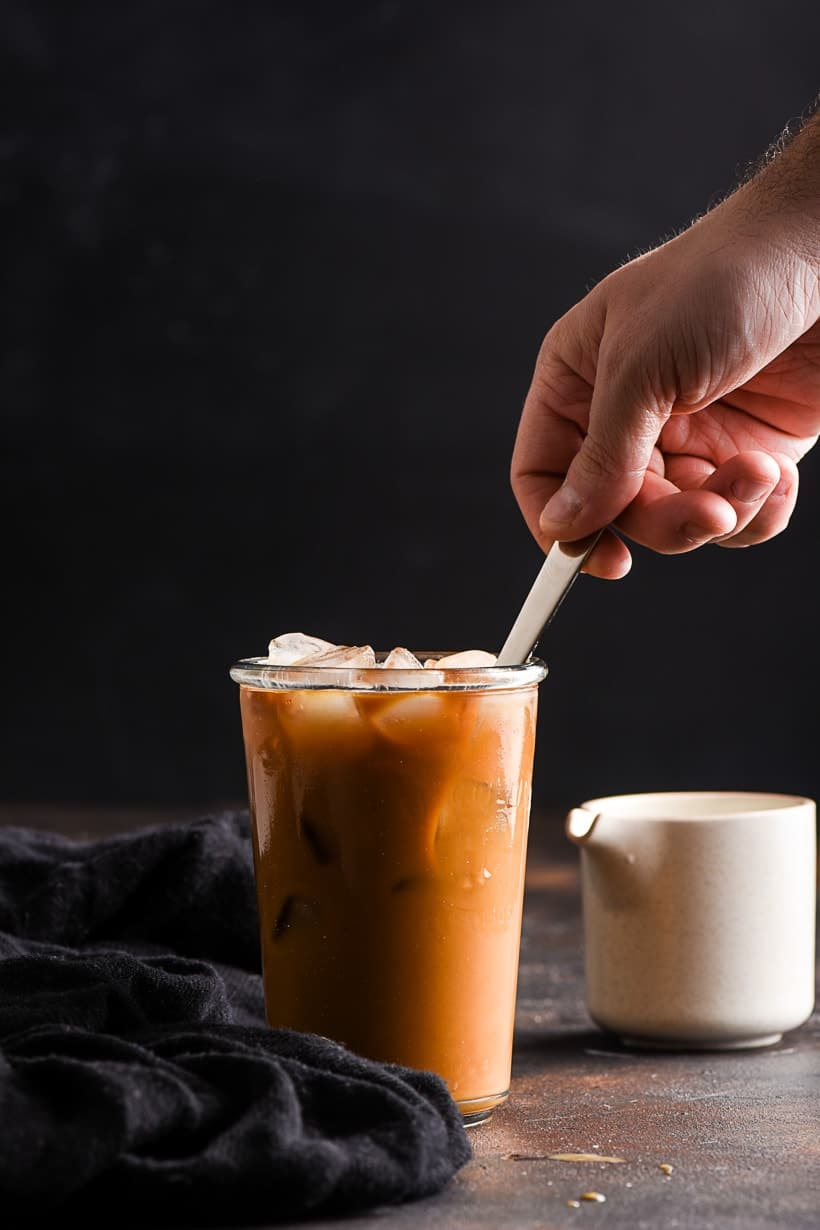 vanilla iced coffee being stirred with a spoon