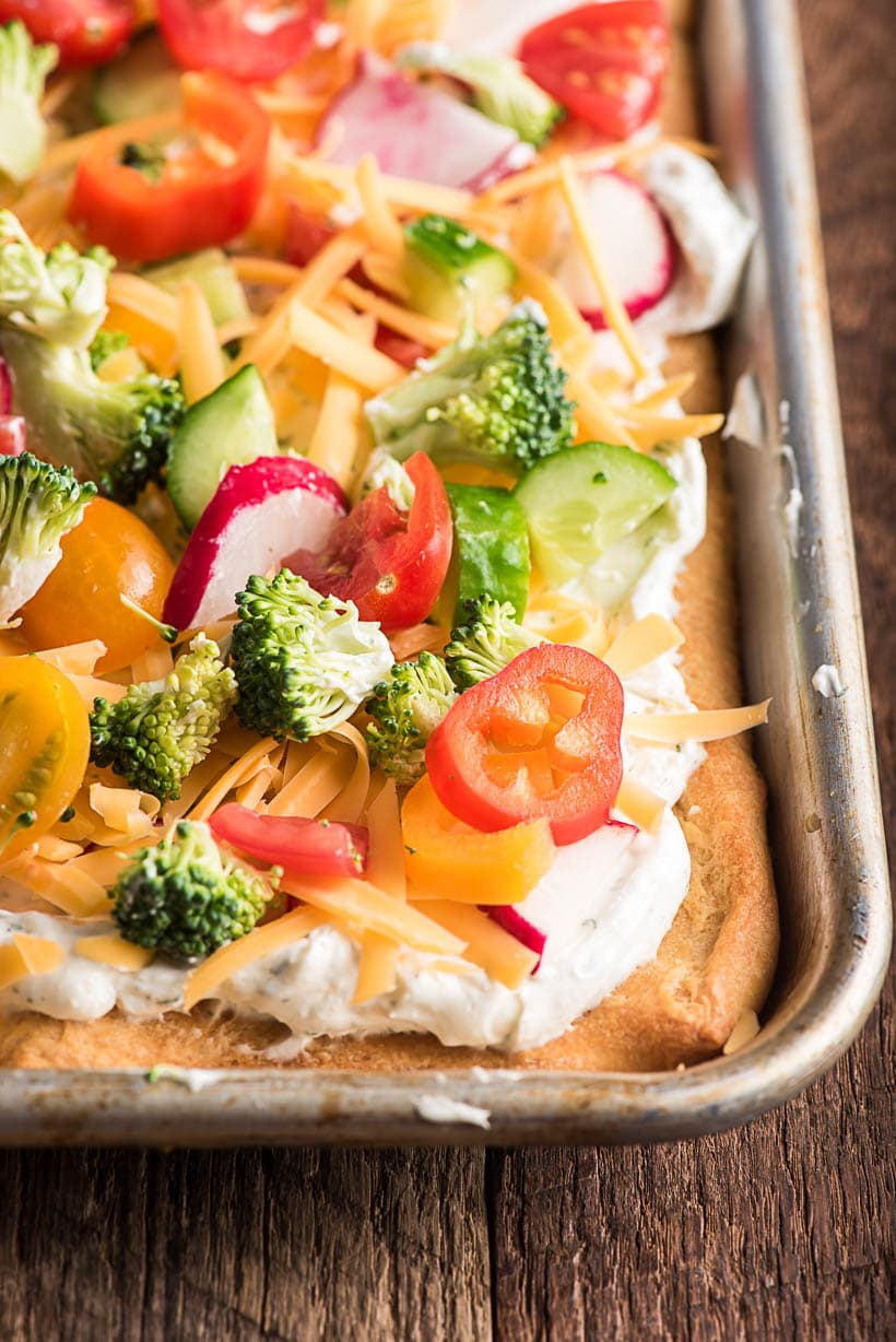 crescent pizza with cream cheese and raw vegetables on top