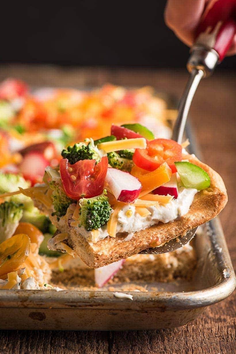 Spatula holding a slice of cold veggie pizza