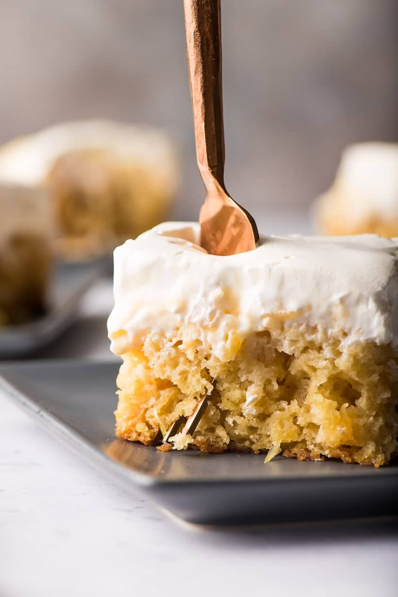 Slice of pineapple sunshine cake with a fork taking off a bite
