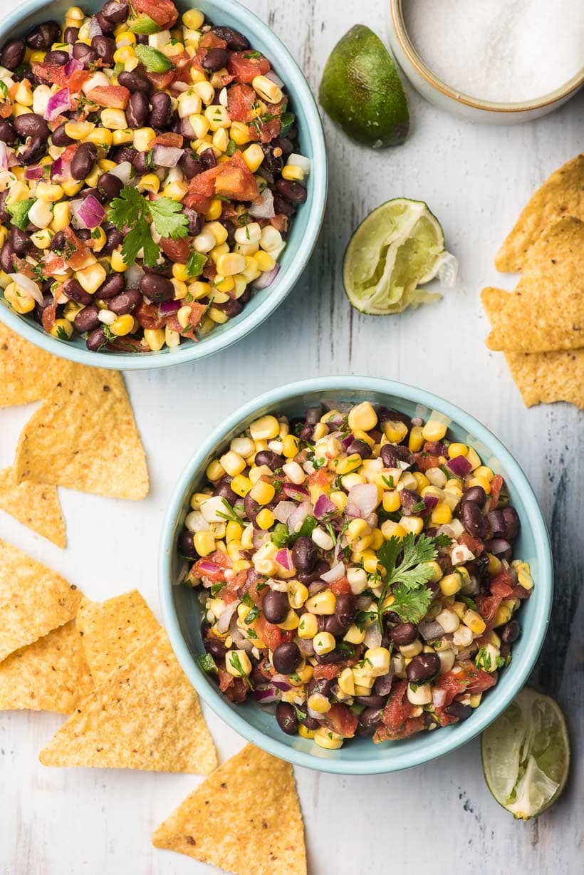 two bowls of black bean corn salsa with tortilla chips and limes