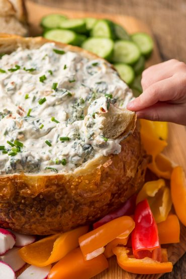 hand dipping a bread chunk into a bread bowl of spinach dip surrounded by fresh vegetables