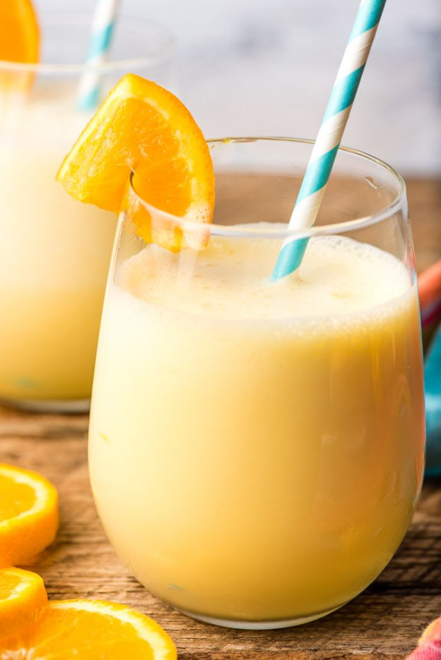 homemade orange julius in a glass with a fresh orange slice