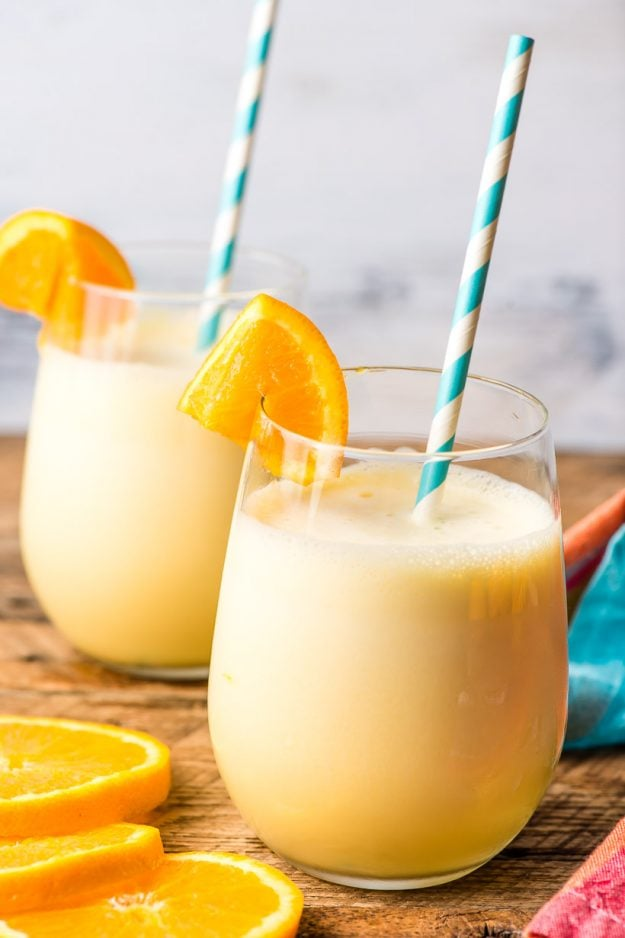 Two glasses of fresh homemade orange julius on a rustic summer table