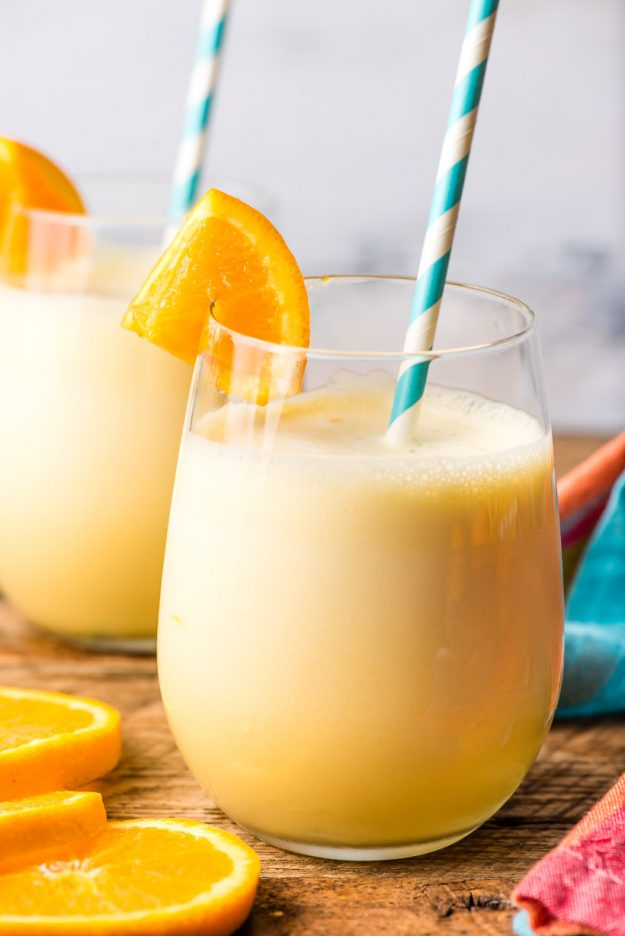 Two glasses of homemade orange julius on a wood table with orange slices