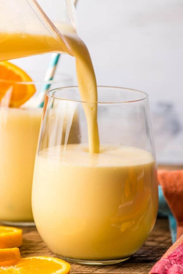 a blender pouring homemade orange julius into a glass
