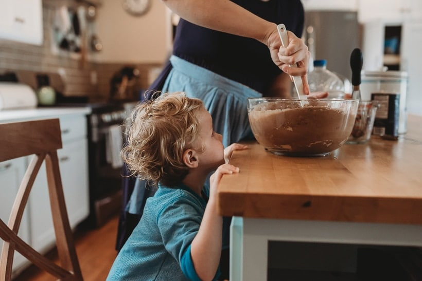 white toddler standing at a kitchen counter looking at a bowl of chocolate cake