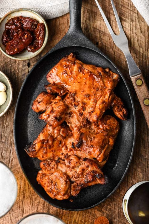 overhead image of grilled chicken in a fajita skillet surrounded by fork and chipotle peppers