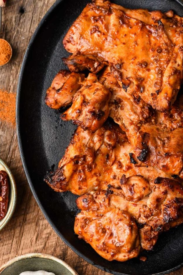 overhead picture of grilled spicy chicken thighs on a skillet