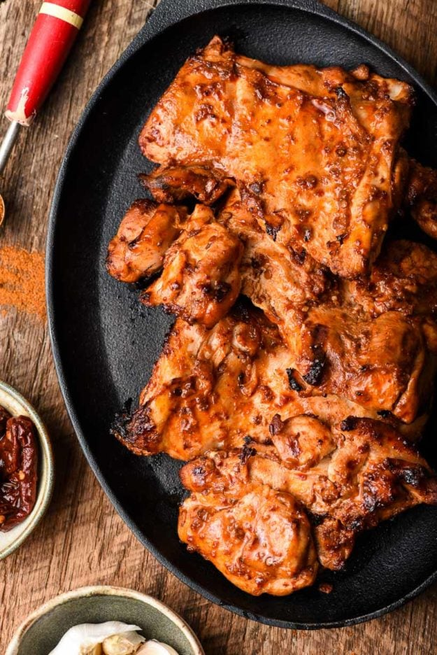grilled chipotle chicken on a skillet surrounded by spices on a table