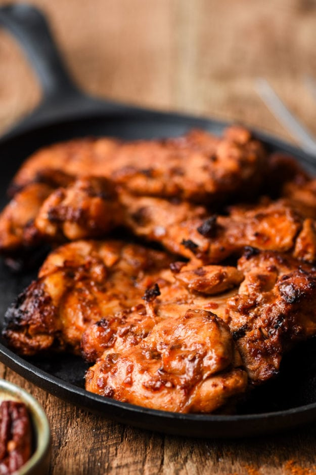 closeup image of spicy grilled chicken served on a skillet