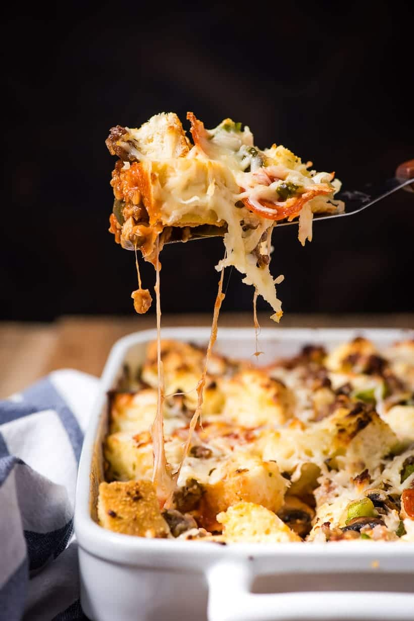 Scoop of garlic bread pizza casserole with melty cheese strings