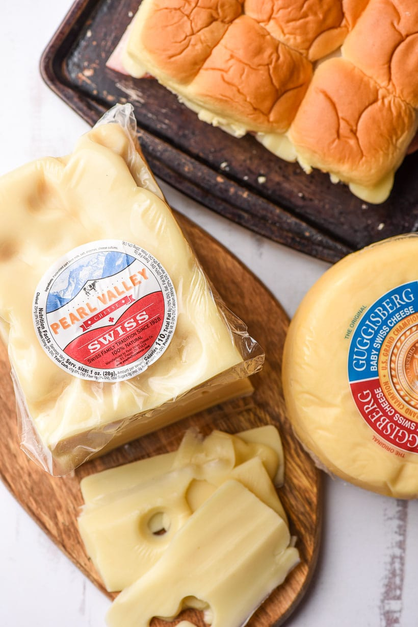 block of Pearl Valley Swiss cheese and wheel of Guggisberg cheese