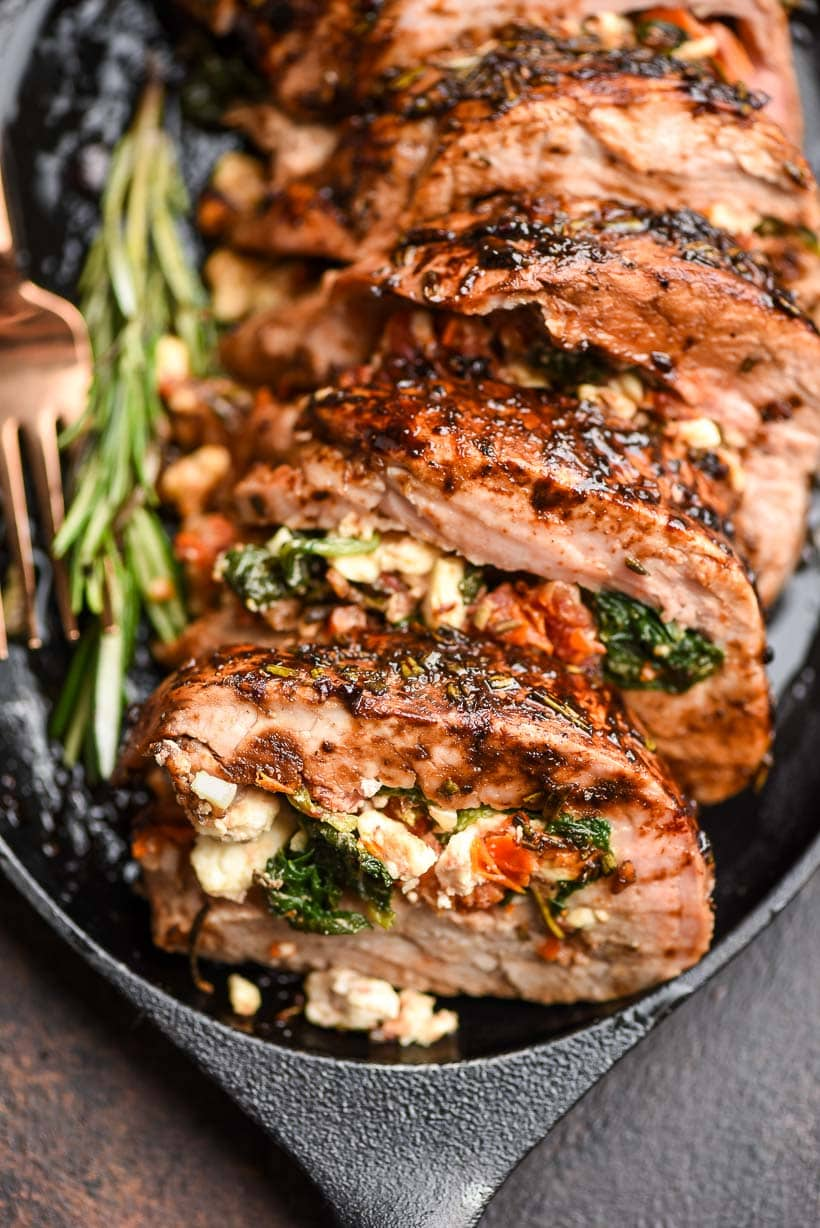 Juicy Pork Tenderloin cuts filled with Mediterranean cheese and herbs is served on a skillet