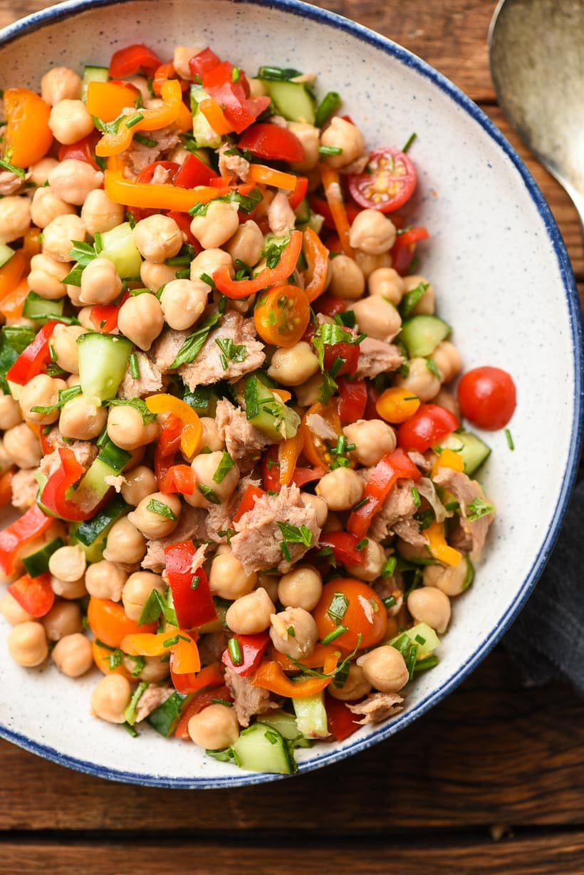 Tuna and Chickpea Salad with fresh vegetables in a white speckled bowl