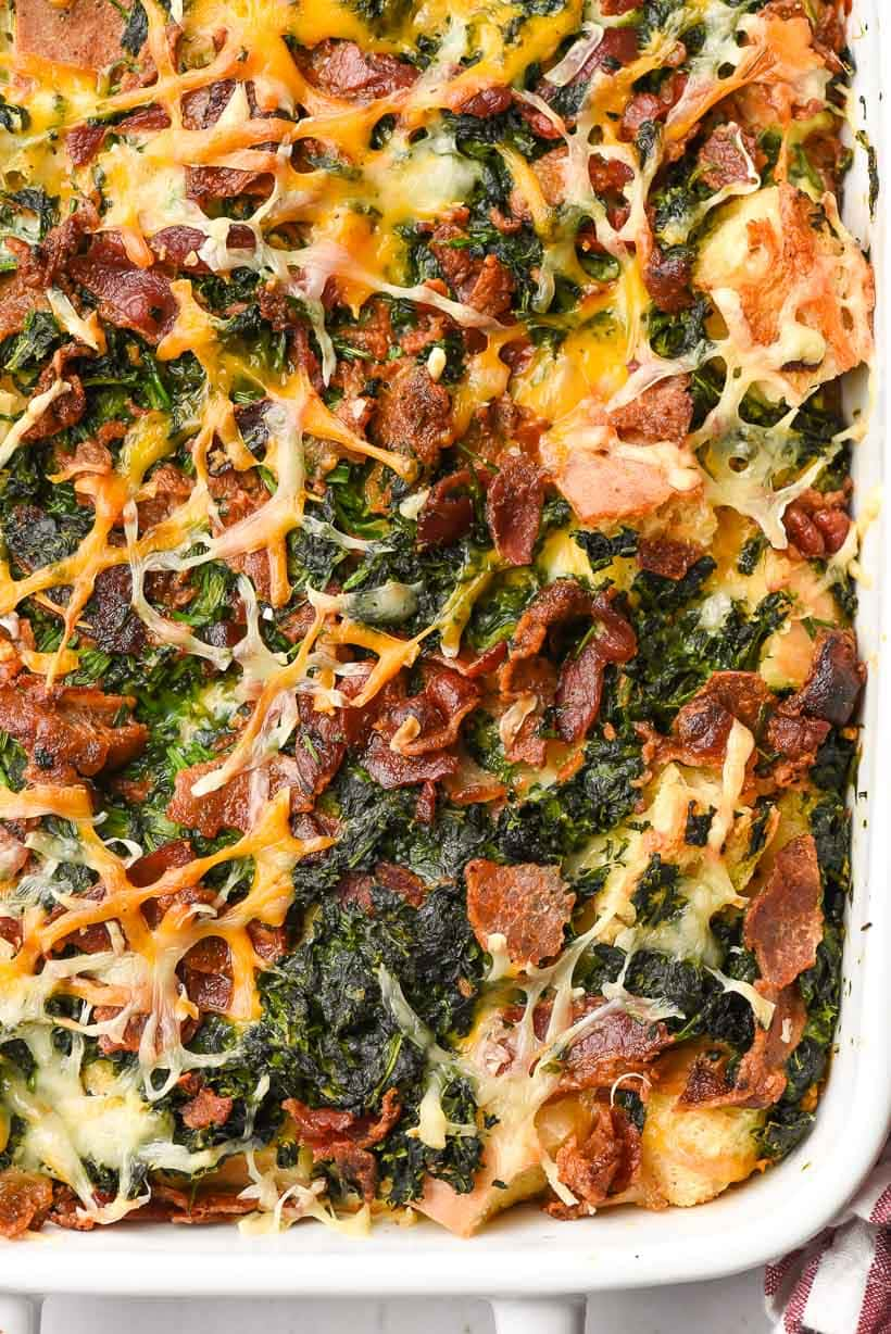 close up of breakfast casserole with bacon, cheese, and spinach