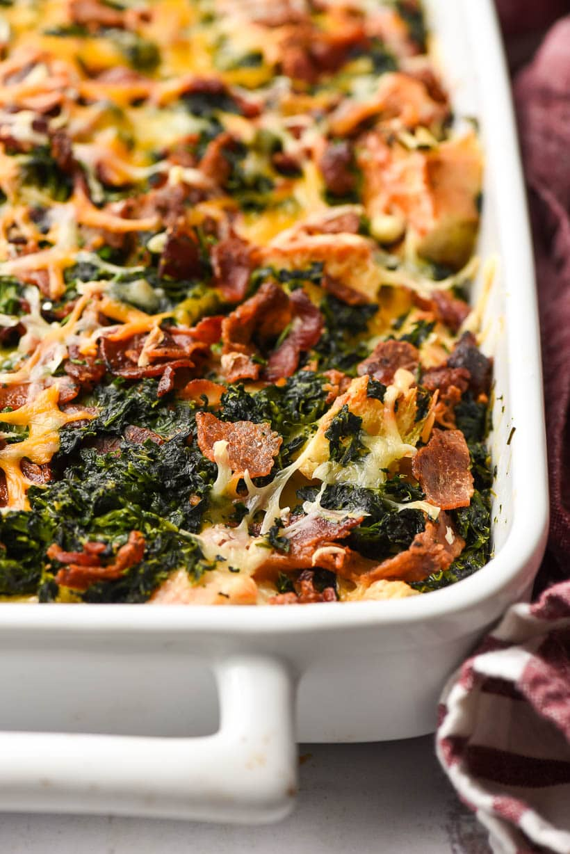 cheesy breakfast casserole with bacon and spinach in a white casserole dish