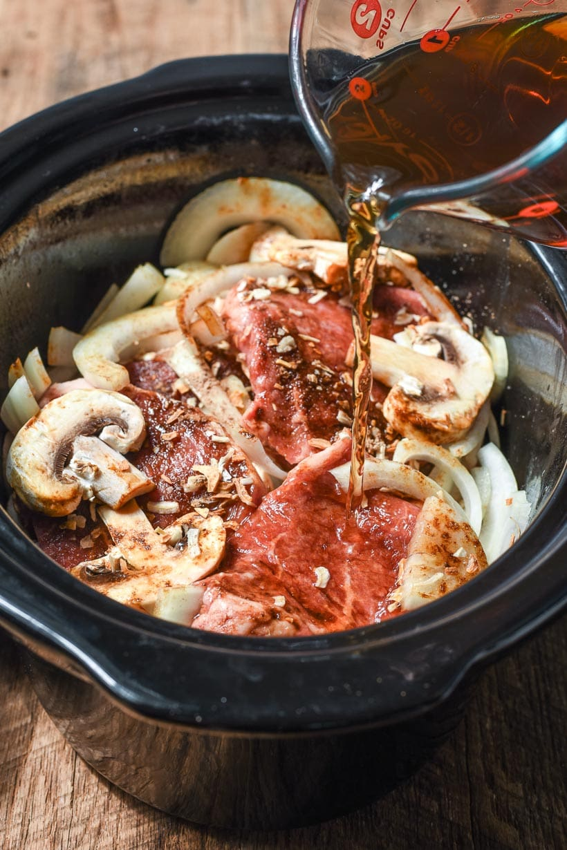 round steaks, mushrooms, and onions in a slow cooker with beef broth pouring over top