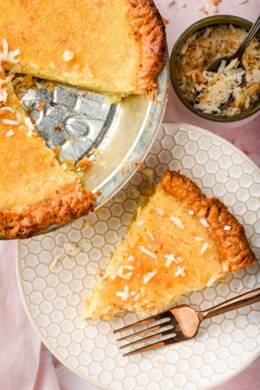 custard pie in a silver pie tin with one sliced removed and plated
