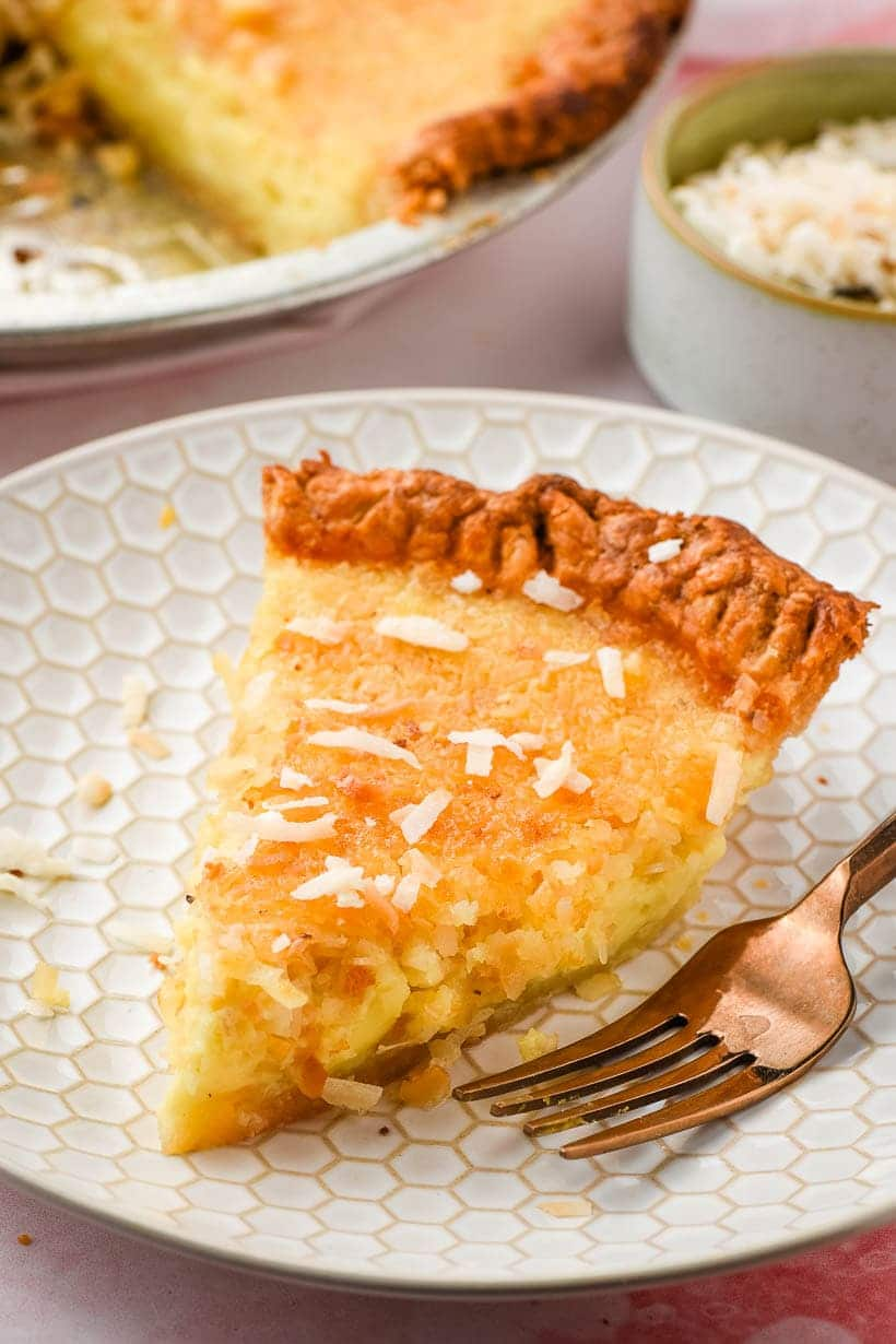 slice of coconut custard pie on a white plate with gold fork