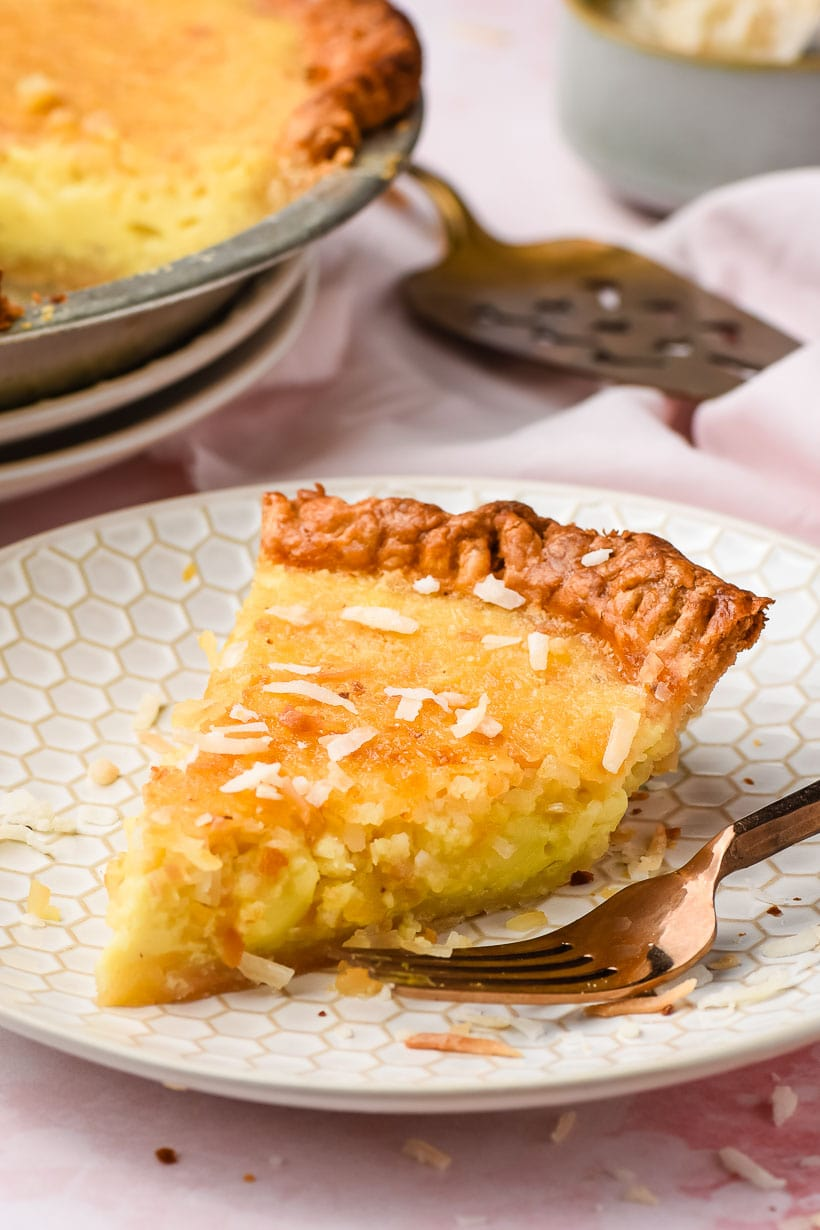 white plate with a slice of coconut custard pie on top