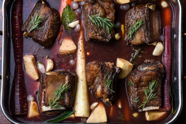 beef short ribs in a roaster with root vegetables and rosemary sprigs