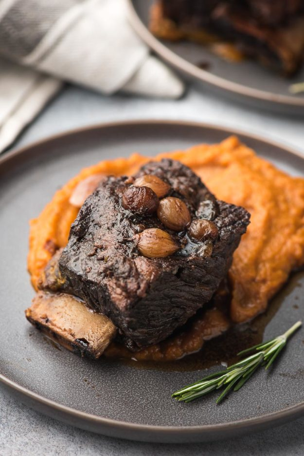 braised short rib with root vegetable puree on a dark gray plate
