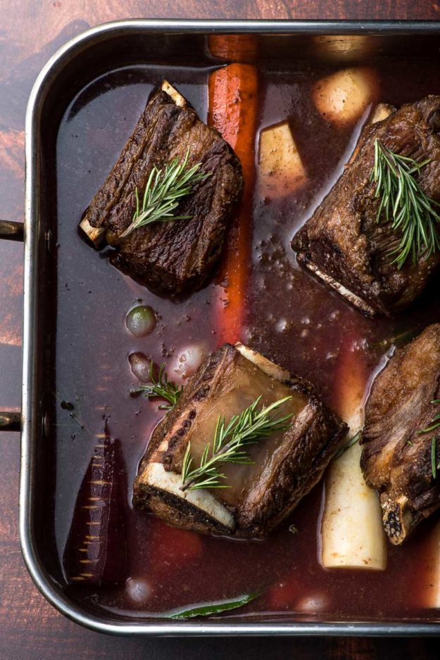 roaster full of oven braised short rib with root vegetables and rosemary