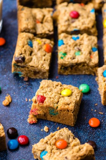 Slices of Monster Cookie Bars arranged on a dark background