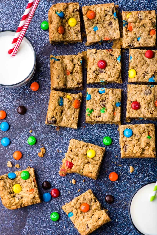 Sliced Monster Cookie Bars beside cups of milk