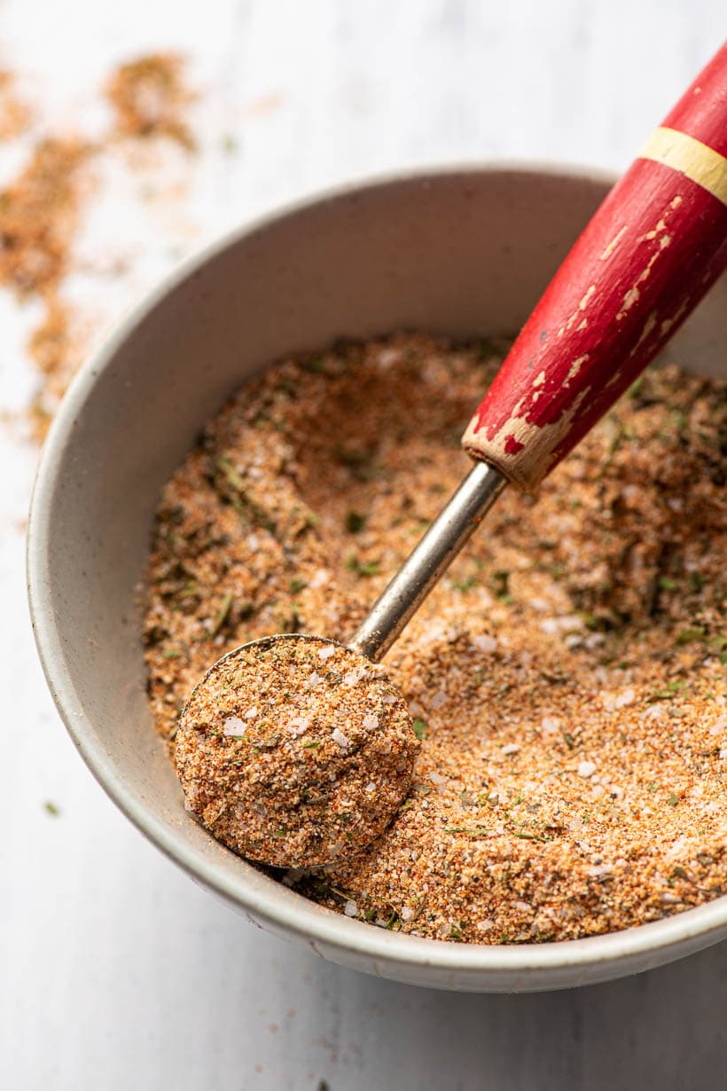 chicken seasoning being scooped out of a bowl