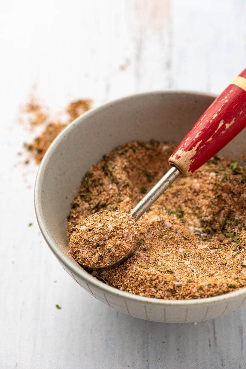teaspoon scooping chicken seasoning out of a bowl