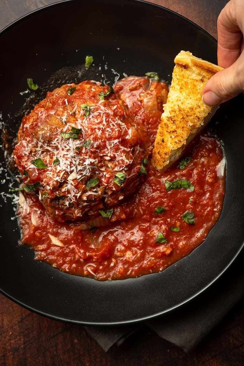 toasted bread dipping into bowl of marinara sauce and meatballs