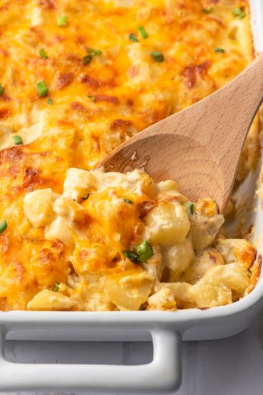 wooden spoon scooping cheesy potatoes