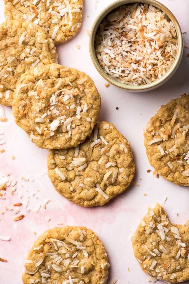 coconut cookies with flaked toasted coconut on a pink background