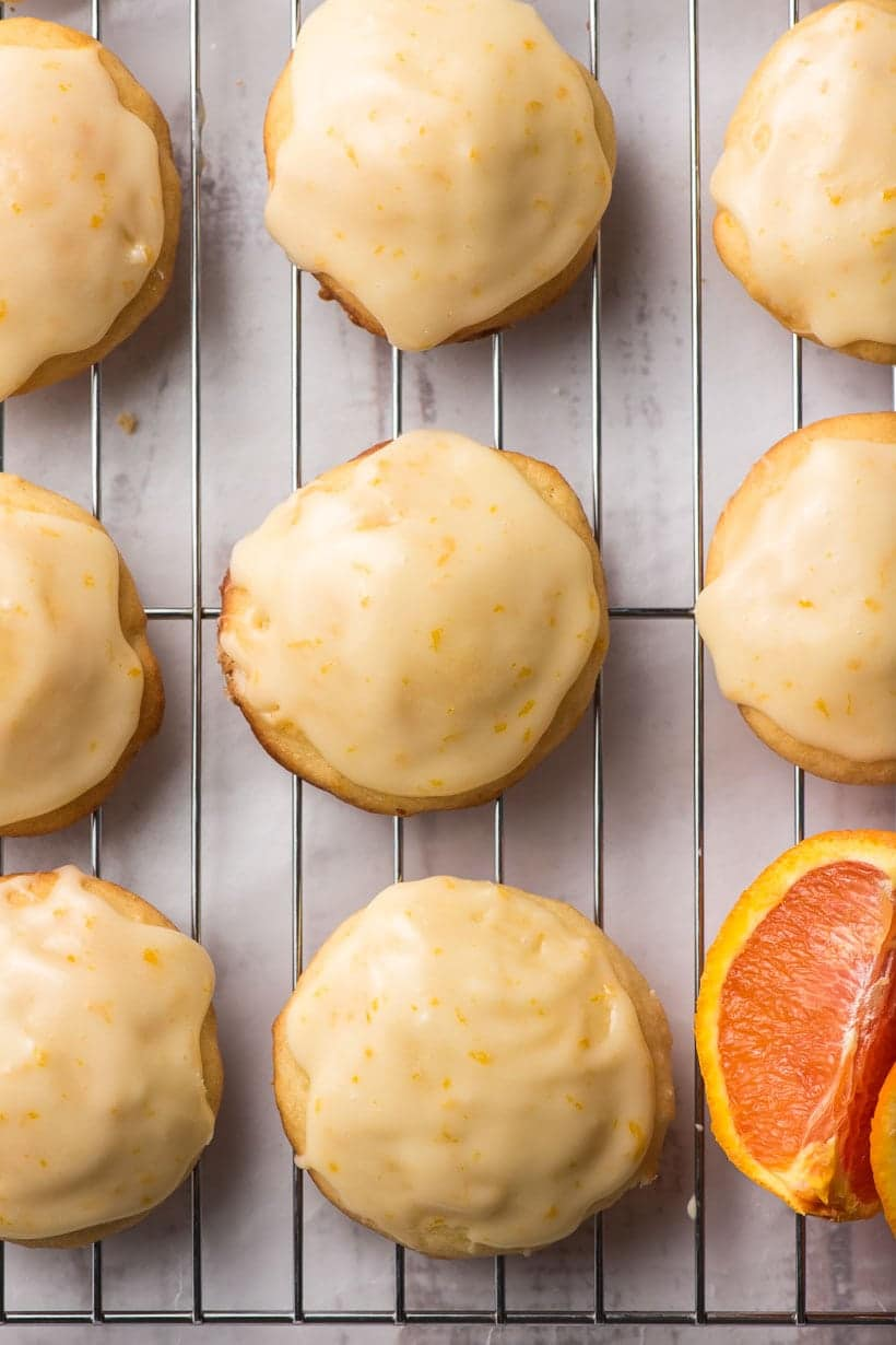 frosted orange cookies on a cooling rack